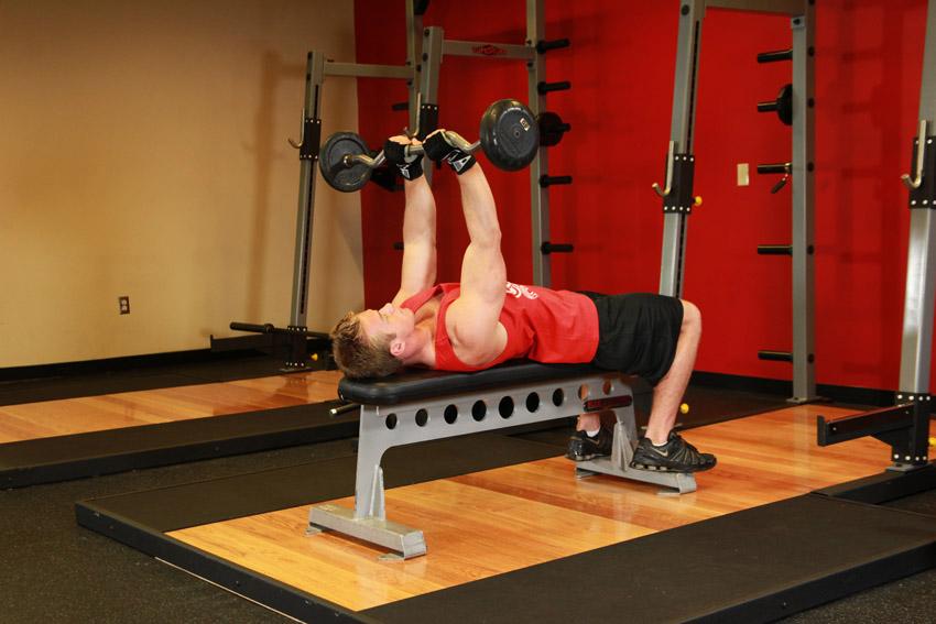 Press de tríceps a la barbilla con barra y agarre cerrado en posición recostada